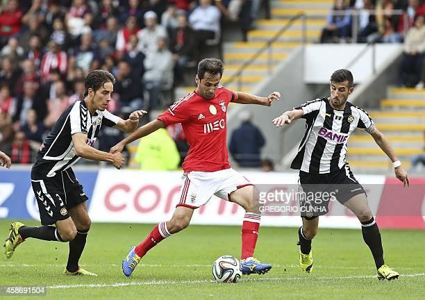 Benfica's Brazilian forward Jonas Oliveira vies with Nacional's midfielder Joao Aurelio and Nacional's midfielder Edgar Abreu during the Portuguese...