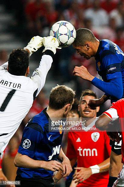 Benfica's Brazilian goalkeeper Artur Moraes blocks a header from Manchester United's defender Chris Smalling during their UEFA Champions League Group...