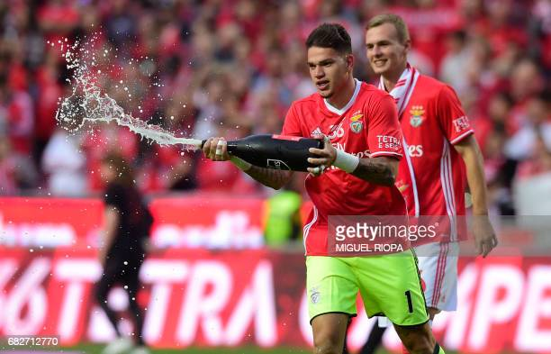 Benfica's Brazilian goalkeeper Ederson Moraes sprays champagneafter winning their 36th title at the end of the Portuguese league football match SL...