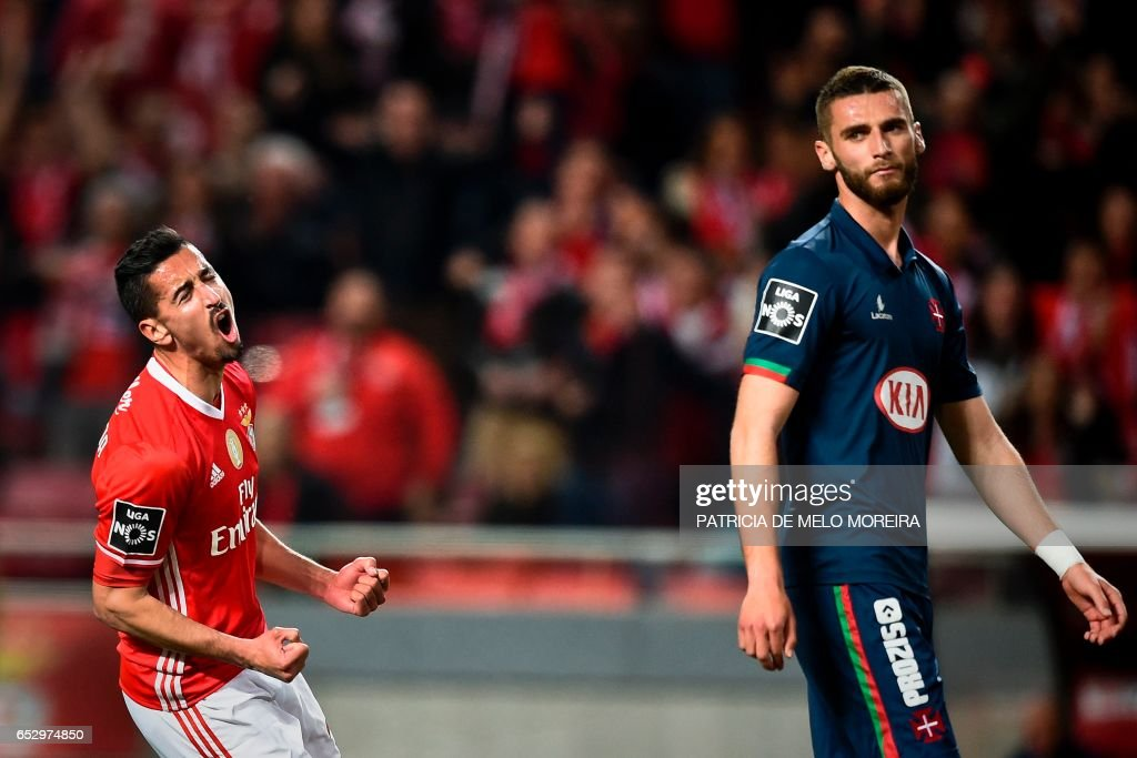 Benfica's defender Andre Almeida (L) celebrates a goal during the Portuguese league football match SL Benfica vs OS Belenenses at the Luz stadium in Lisbon on March 13, 2017. /