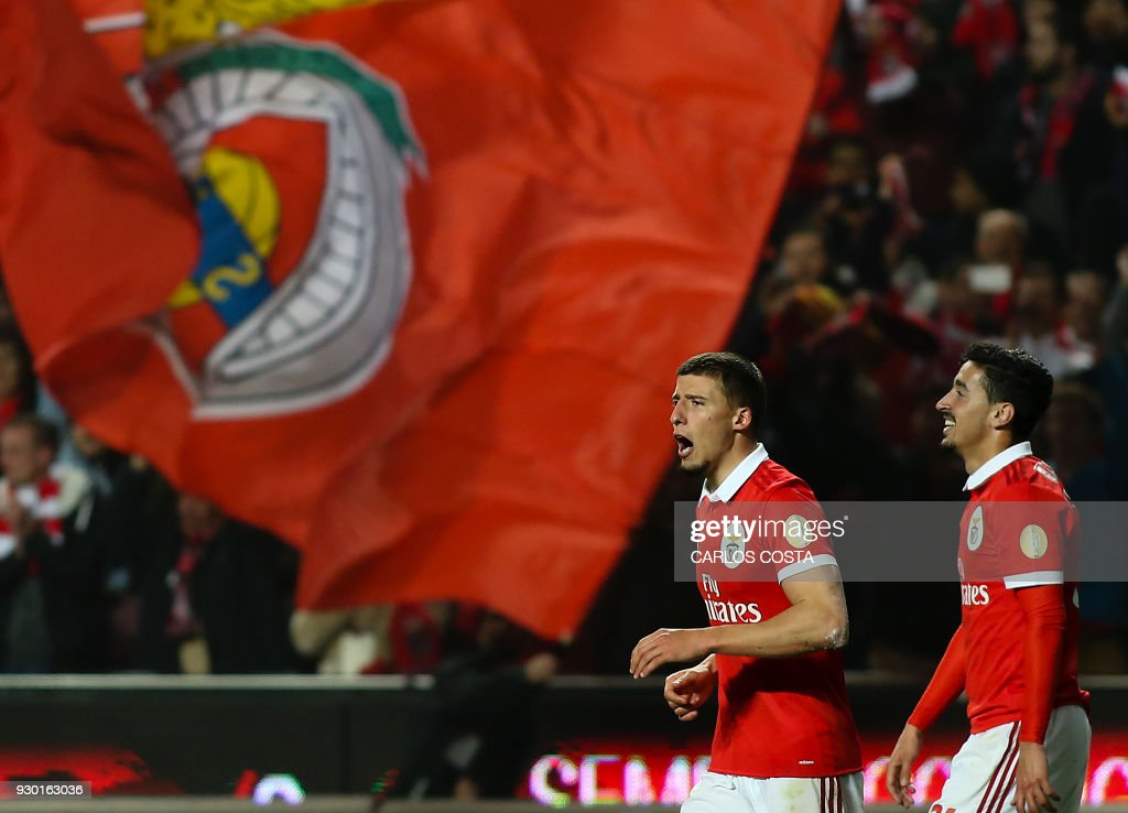 Benfica's defender Ruben Dias (L) celebrates a goal with Benfica's defender Andre Almeida during the Portuguese league football match between SL Benfica and CD Aves at the La Luz stadium in Lisbon on March 10, 2018. /