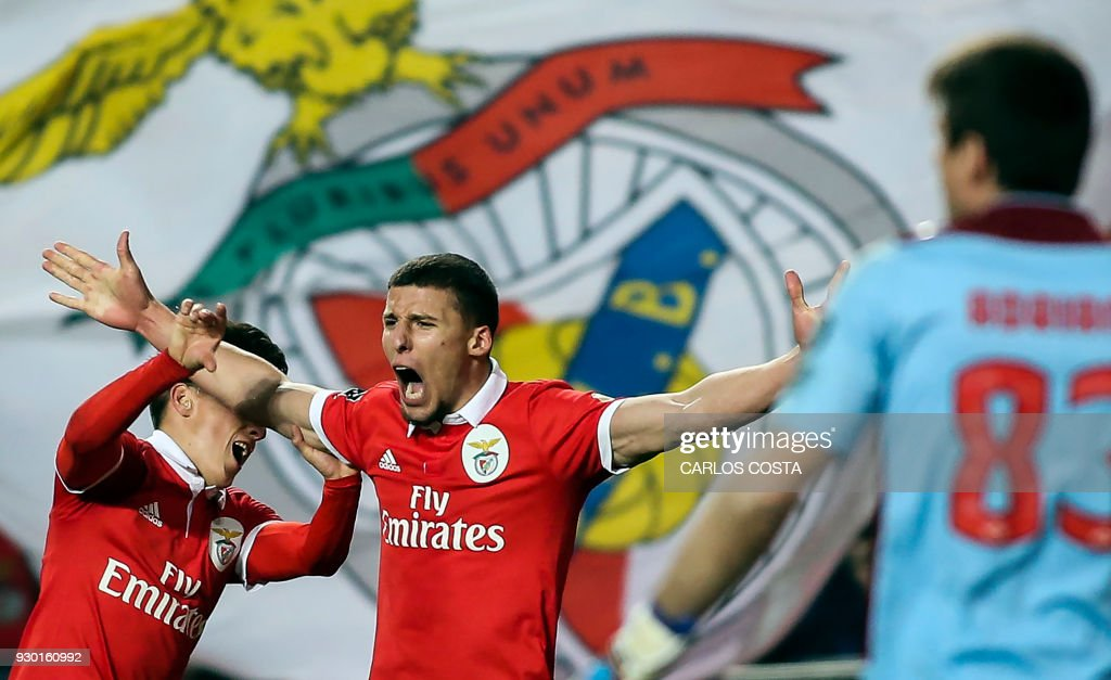 Benfica's defender Ruben Dias celebrates a goal with Benfica's Argentinian forward Franco Cervi (L) during the Portuguese league football match between SL Benfica and CD Aves at the La Luz stadium in Lisbon on March 10, 2018. /