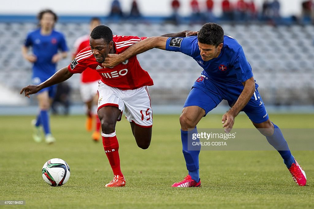 Benfica's Dutch forward Ola John (L) vies with Belenenses's defender Joao Afonso (R) during the Portuguese league football match CF Os Belenenses v SL Benfica at the Restelo stadium in Lisbon on April 18, 2015.
