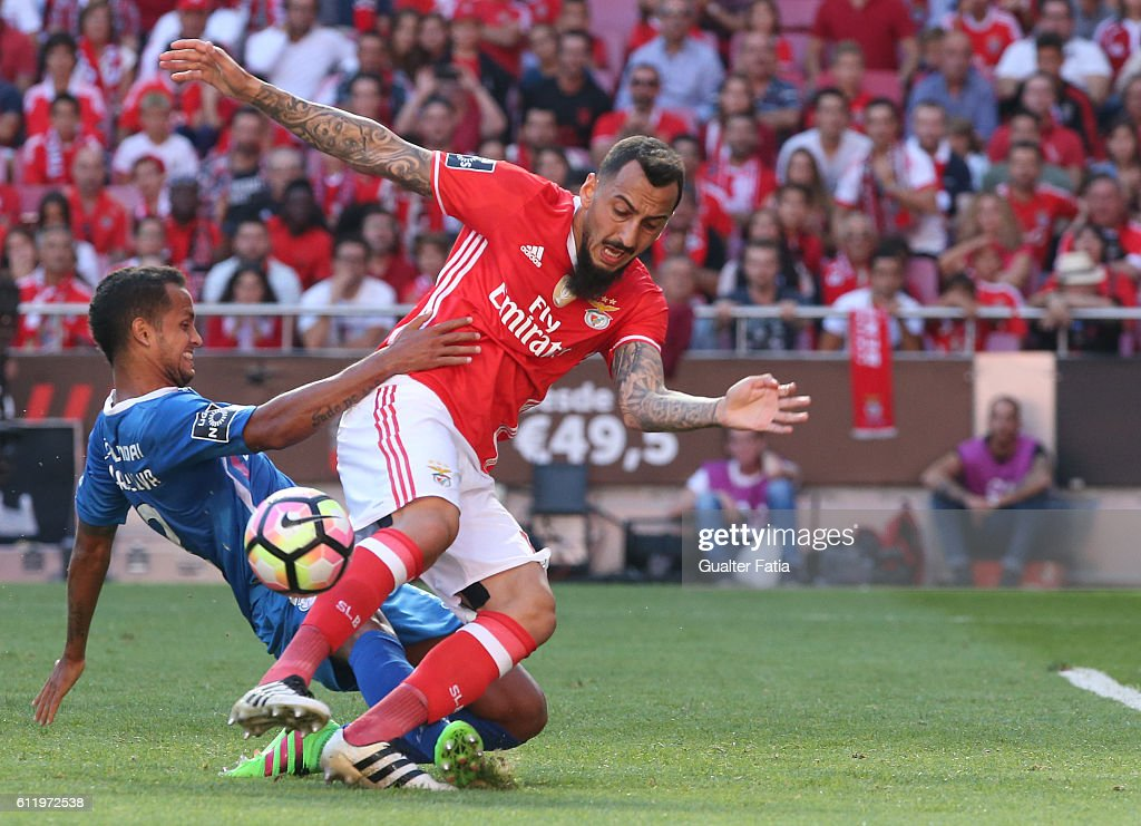 SL Benfica's forward from Greece Kostas Mitroglou tackled by Feirense's defender Icaro Silva from Brasil during the Primeira Liga match between SL Benfica and CD Feirense at Estadio da Luz on October 2, 2016 in Lisbon, Portugal.