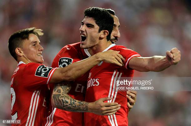 Benfica's forward Goncalo Guedes celebrates his goal with teammate Greek forward Konstantinos Mitroglou and Benfica's Argentinian forward Franco...