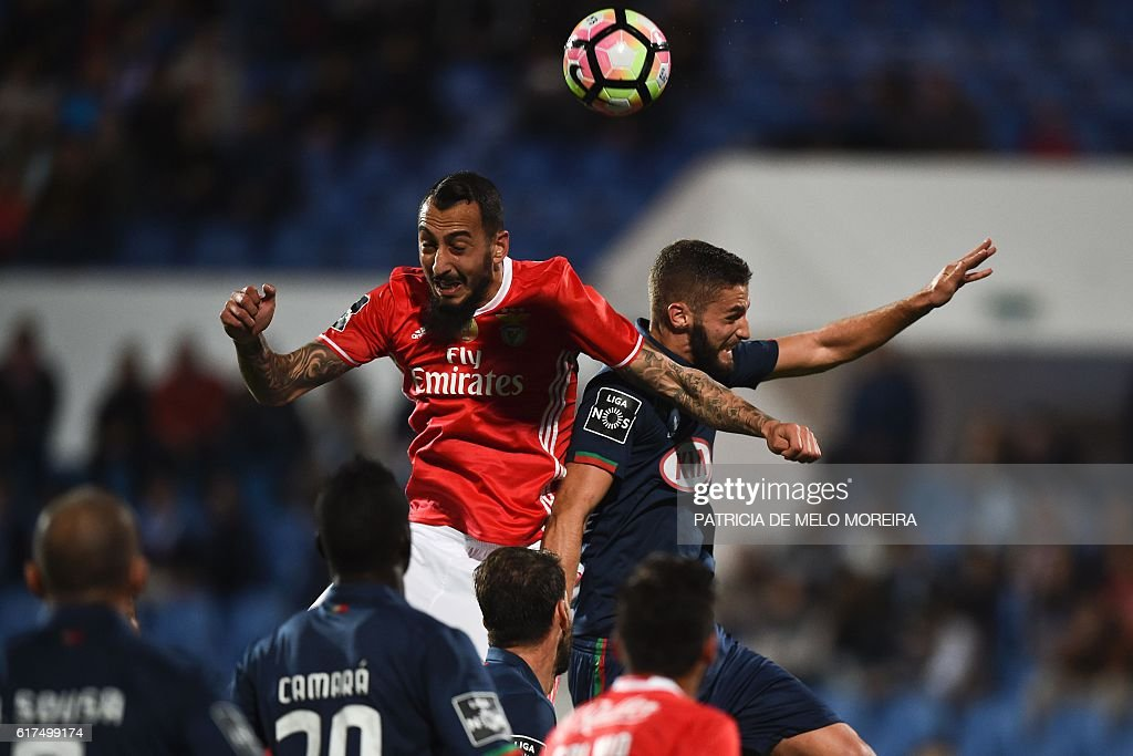 Benfica's Greek forward Konstantinos Mitroglou (L) heads the ball to score a goal beside Belenenses' defender Domingos Duarte (R) during the Portuguese league football match between OS Belenenses and SL Benfica at the Restelo stadium in Lisbon on October 23, 2016. / AFP / PATRICIA