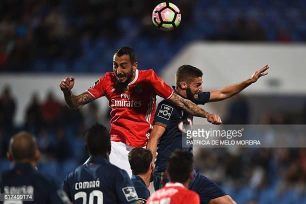 Benfica's Greek forward Konstantinos Mitroglou heads the ball to score a goal beside Belenenses' defender Domingos Duarte during the Portuguese...