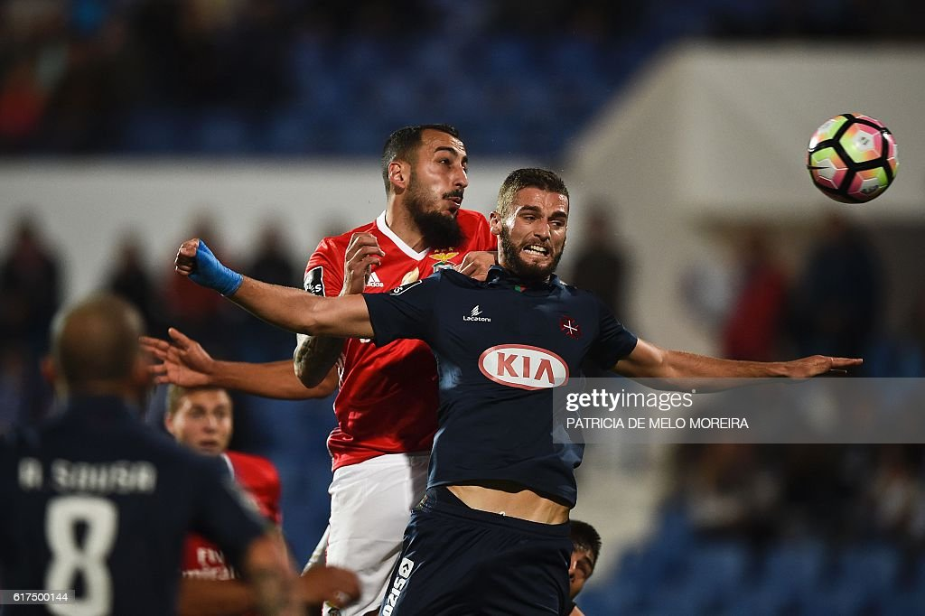 Benfica's Greek forward Konstantinos Mitroglou (L) heads the ball with Belenenses' defender Domingos Duarte during the Portuguese league football match between OS Belenenses and SL Benfica at the Restelo stadium in Lisbon on October 23, 2016. / AFP / PATRICIA