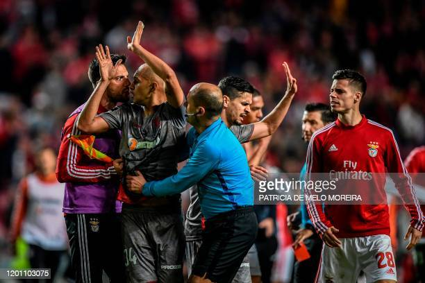 Benfica's Greek midfielder Andreas Samaris argues with Braga's Brazilian defender Raul Silva as the Portuguese referee Hugo Miguel tries to separate...
