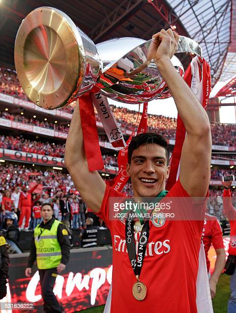 Benfica's Mexican forward Raul Jimenez holds the trophy to celebrate Benfica's 35th Portuguese league title at the end of the Portuguese league...