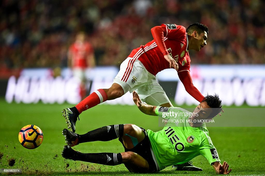 Benfica's Mexican forward Raul Jimenez (Up) vies with Rio Ave's defender Roderick Miranda during the Portuguese league football match SL Benfica vs Rio Ave FC at the Luz stadium in Lisbon on December 21, 2016. / AFP / PATRICIA