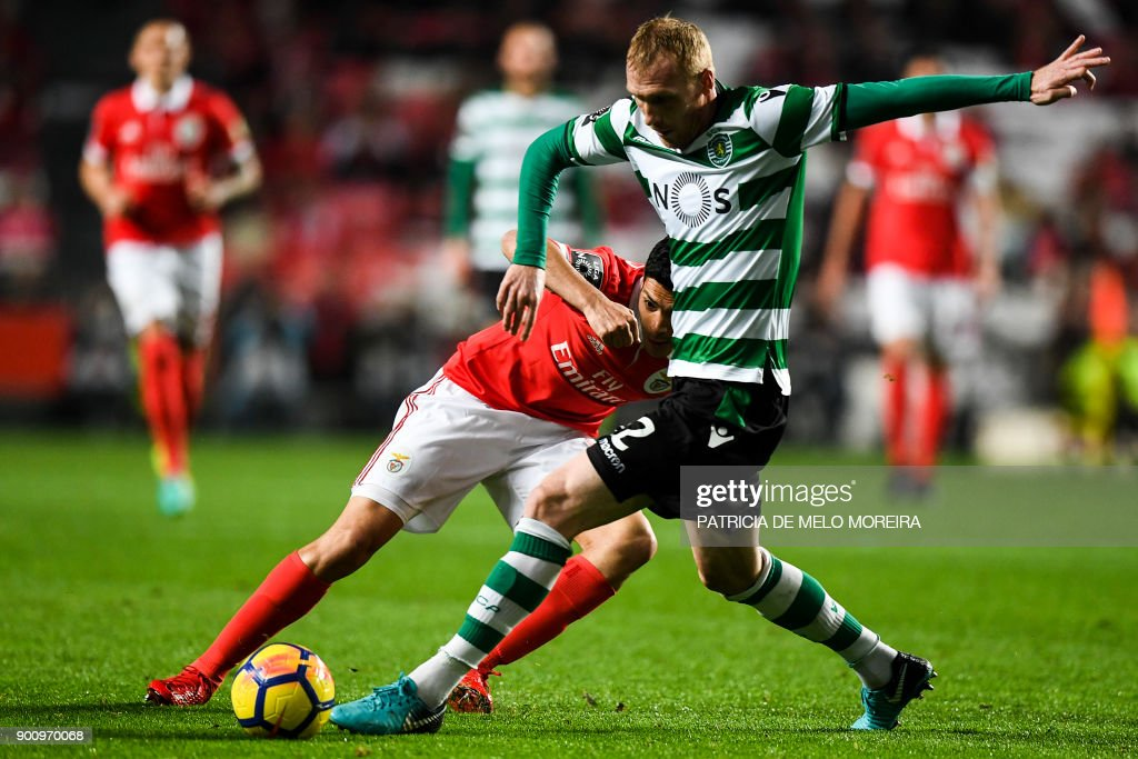Benfica's Mexican forward Raul Jimenez (L) vies with Sporting's French defender Jeremy Mathieu during the Portuguese league football match SL Benfica vs Sporting CP at the Luz stadium in Lisbon on January 3, 2018. /