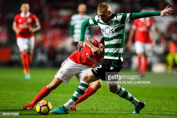 Benfica's Mexican forward Raul Jimenez vies with Sporting's French defender Jeremy Mathieu during the Portuguese league football match SL Benfica vs...