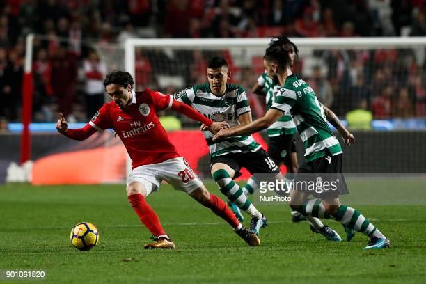 Benfica's midfielder Filip Krovinovic vies for the ball with Sporting's midfielder Rodrigo Battaglia and Sporting's midfielder Bruno Fernandes during...