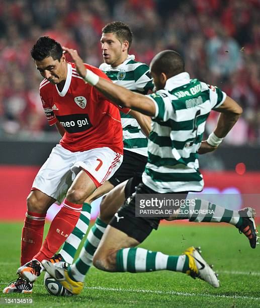Benfica's paraguayan forward Oscar Cardozo fights for the ball with Sporting's US defender, Onyewu during their Portuguese league football match at...