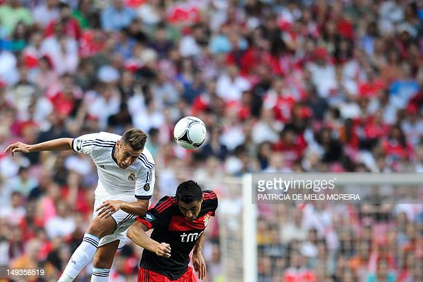 Benfica's Paraguayan forward Oscar Cardozo heads the ball as he competes with Real Madrid's midfielder Alex Fernandez during their Eusebio Cup...
