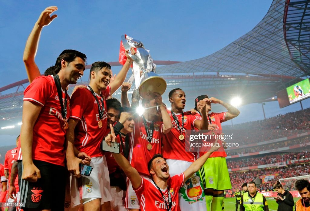 Benfica's players hold the cup after winning their 36th title at the end of the Portuguese league football match SL Benfica vs Vitoria Guimaraes SC at the Luz stadium in Lisbon on May 13, 2017. Lisbon giants Benfica clinched a fourth straight Portuguese league title on May 13, 2017 with a 5-0 victory over Vitoria Guimaraes. The champions have an unassailable 81 points from 33 games and cannot be caught by Porto, who are eight points behind with just two games to play. /