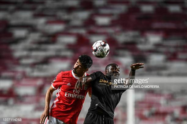 TOPSHOT Benfica's Portuguese defender Andre Almeida heads the ball with Guimaraes Dutch forward Ola John during the Portuguese League football match...
