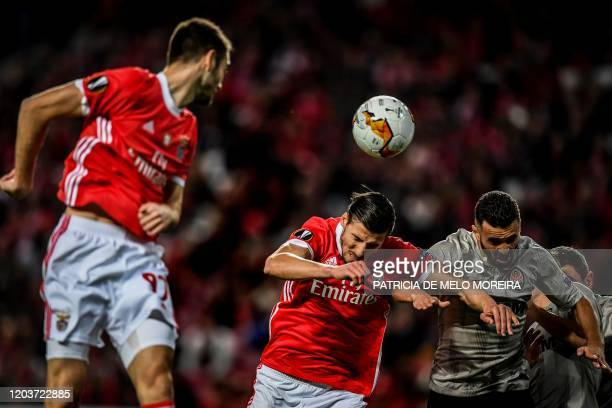 Benfica's Portuguese defender Ruben Dias heads the ball with Shakhtar's Ukranian forward Junior Moraes during the UEFA Europa League round of 32...