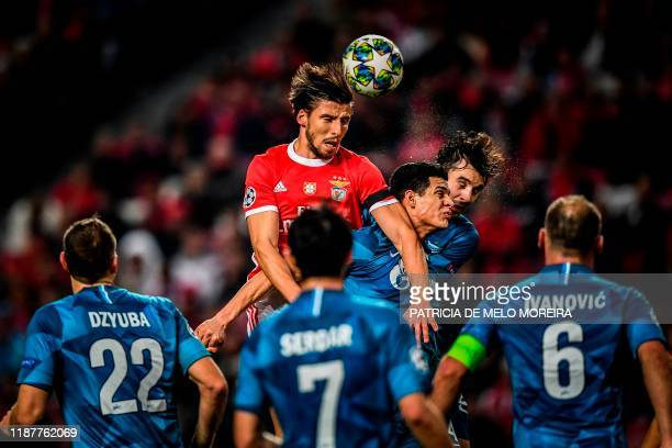Benfica's Portuguese defender Ruben Dias heads the ball with Zenit's Venezuelan defender Yordan Osorio and Zenit's Russian midfielder Aleksandr...