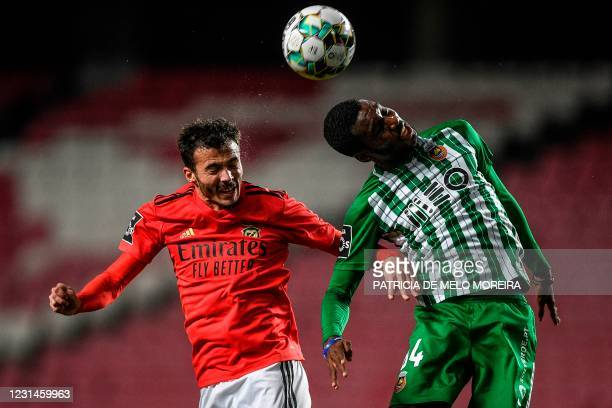 Benfica's Portuguese midfielder Diogo Gonclaves heads the ball with Rio Ave's Portuguese forward Rafael Camacho during the Portuguese league football...