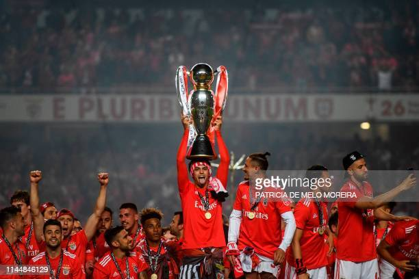 Benfica's Portuguese midfielder Joao Felix holds the trophy after Benfica won the Portuguese League Championship at the end of the Portuguese League...