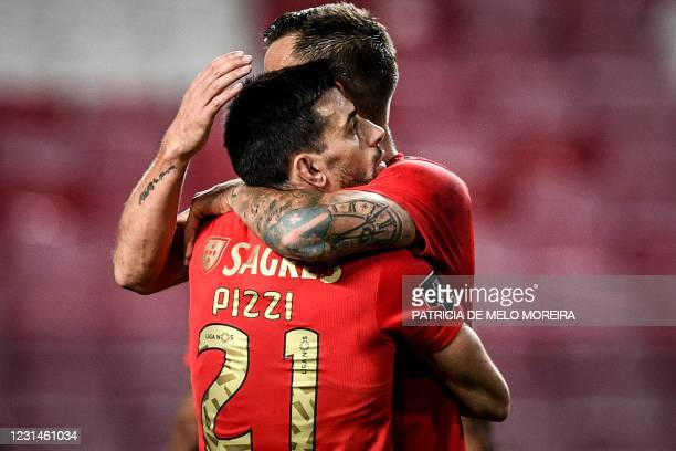 Benfica's Portuguese midfielder Pizzi Fernandes hugs his teammate Benfica's Swiss forward Haris Seferovic at the end of the Portuguese league...