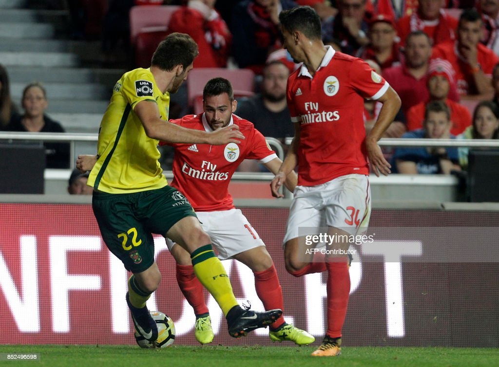 Benfica's Serbian forward Andrija Zivkovic (C) vies with Pacos Ferreira's defender Miguel Vieira (L) past and his teammate defender Andre Almeida during the Portuguese league football match SL Benfica vs FC Pacos de Ferreira at the Luz stadium in Lisbon on September 23, 2017. /