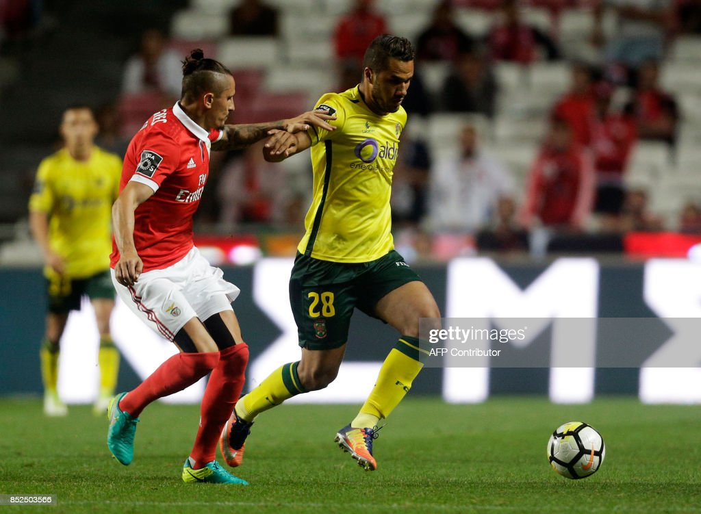 Benfica's Serbian midfielder Ljubomir Fejsa (L) vies with Pacos Ferreira's Brazilian forward Luiz Phellype during the Portuguese league football match SL Benfica vs FC Pacos de Ferreira at the Luz stadium in Lisbon on September 23, 2017. /