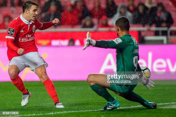 Benfica's Spanish midfielder Alex Grimaldo shoots in front of Maritimo's Brazilian goalkeeper Charles to score a goal during the Portuguese league...