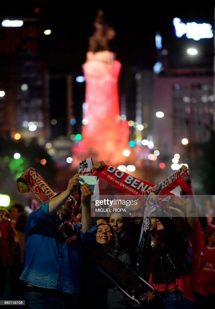 Benfica's supporters take pictures as they gather at Marques de Pombal square in downtown Lisbon on May 13, 2017 to celebrate their team's victory in the 2016-2017 Portuguese League championship. Lisbon giants Benfica clinched a fourth straight Portuguese league title on May 13, 2017 with a 5-0 victory over Vitoria Guimaraes. The champions have an unassailable 81 points from 33 games and cannot be caught by Porto, who are eight points behind with just two games to play. /