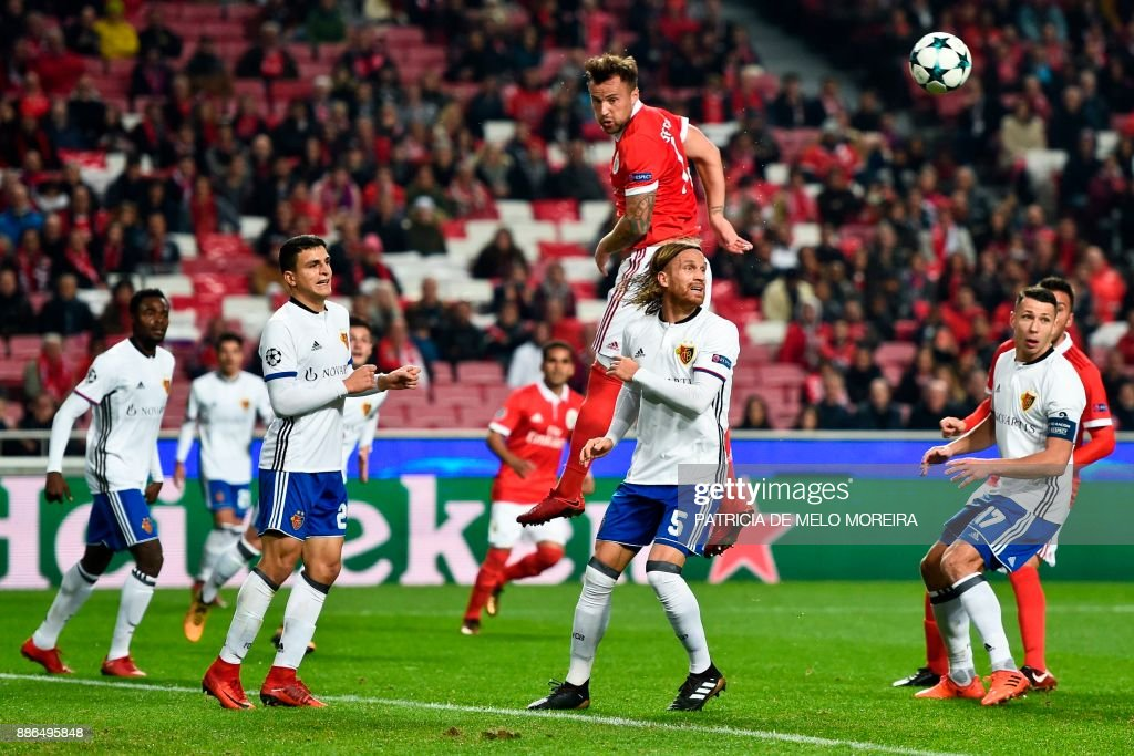 Benfica's Swiss forward Haris Seferovic (top C) heads the ball past Basel's defender Michael Lang (C) during the UEFA Champions League football match SL Benfica vs FC Basel at the Luz stadium in Lisbon on December 5, 2017. /