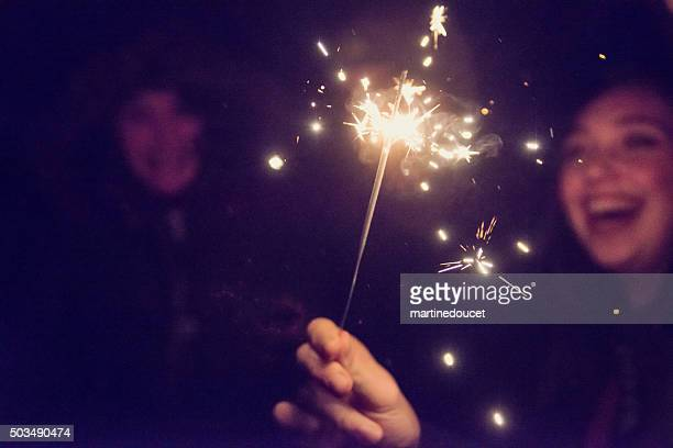bengal fire sparkling in front of woman outdoors at night. - bengal new year stock photos and pictures