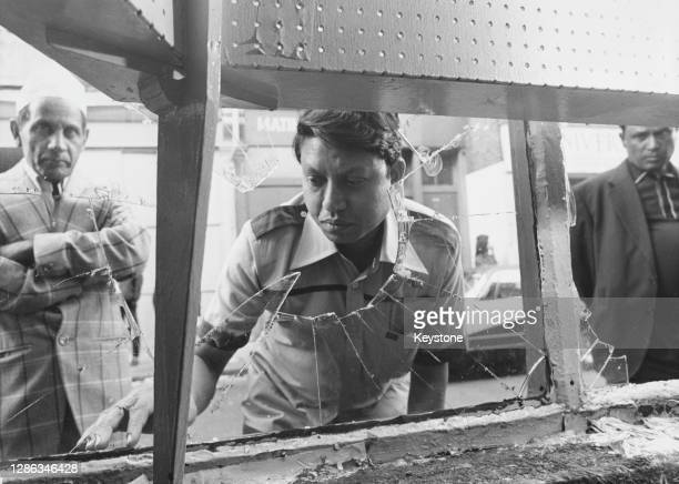 Bengali businessman Abdul Khalique examines the broken window of his shop damaged when a group of over 100 teenagers tore through Brick Lane in a...