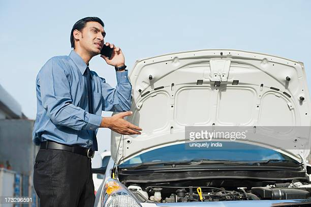 Bengali businessman standing near a broken down car and talking on a mobile phone