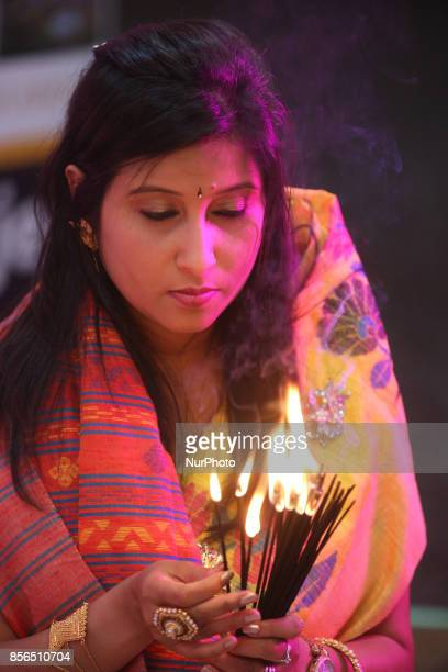 Bengali Hindu woman lights incense while offering prayers during the Durga Puja festival at a pandal in Mississauga Ontario Canada Hundreds of...