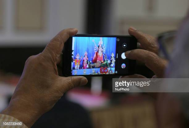 Bengali Hindus take photos of the idol of the Goddess Durga during the Durga Puja festival at a pandal in Mississauga Ontario Canada on October 14...