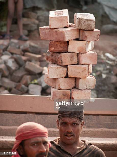 bengali man carrying bricks on his head - khulna stock photos and pictures
