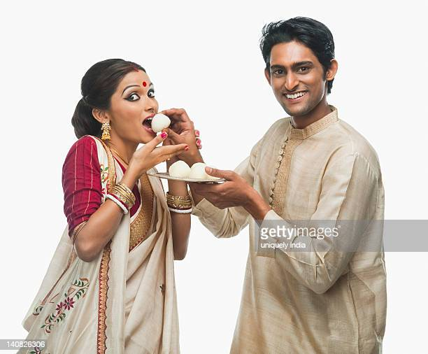 bengali man feeding a rasgulla to his wife - kurta stock pictures, royalty-free photos & images