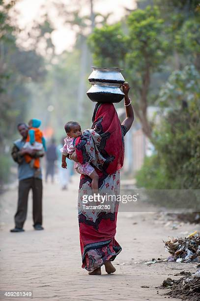 bengali woman carrying baby and water jar in village - bangladesh mother stock pictures, royalty-free photos & images