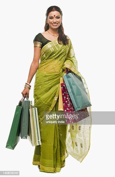 Bengali woman carrying shopping bags and smiling