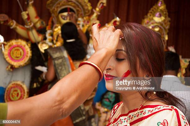 Bengali woman celebrating Durga Puja applying vermilion to each other