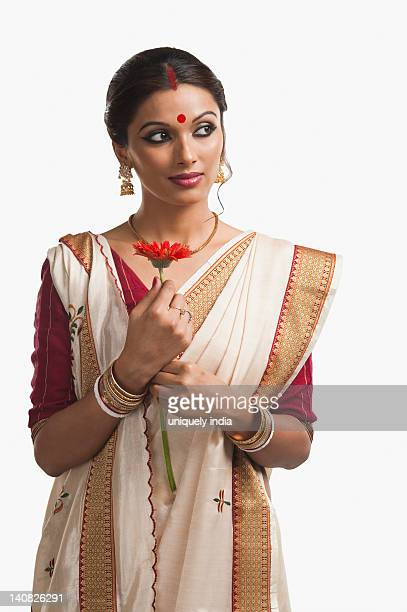 Bengali woman holding a Daisy flower and day dreaming
