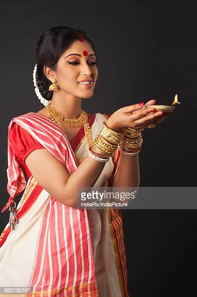 Bengali woman holding a diya