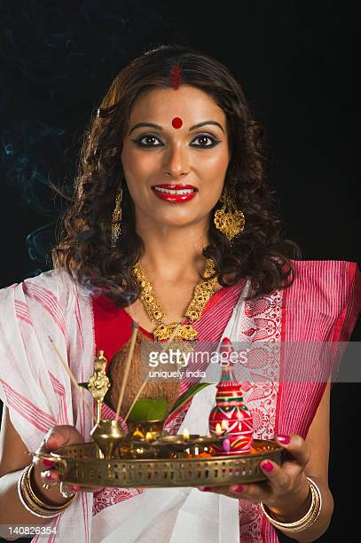Bengali woman holding a pooja thali and smiling