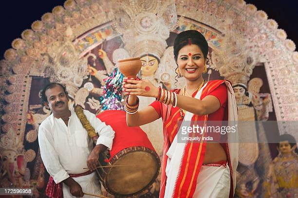 bengali woman performing dhunachi dance and a dhaki playing dhak at durga puja - durga stock photos and pictures