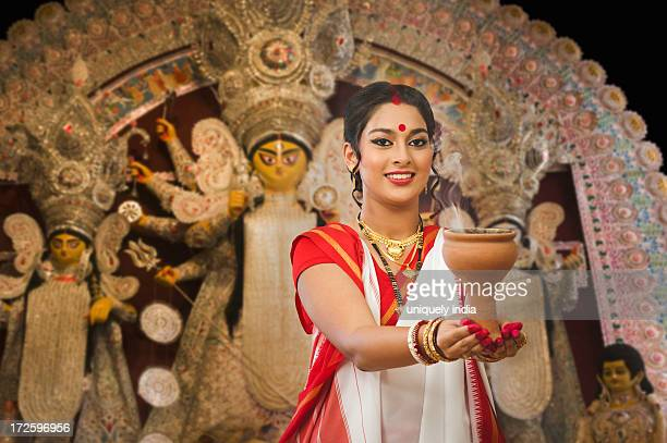 bengali woman performing dhunachi dance at durga puja - durga stock photos and pictures