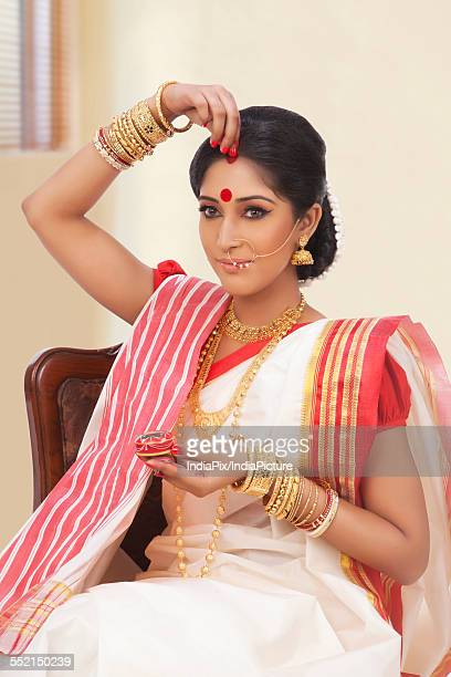 Bengali woman putting sindoor on her forehead