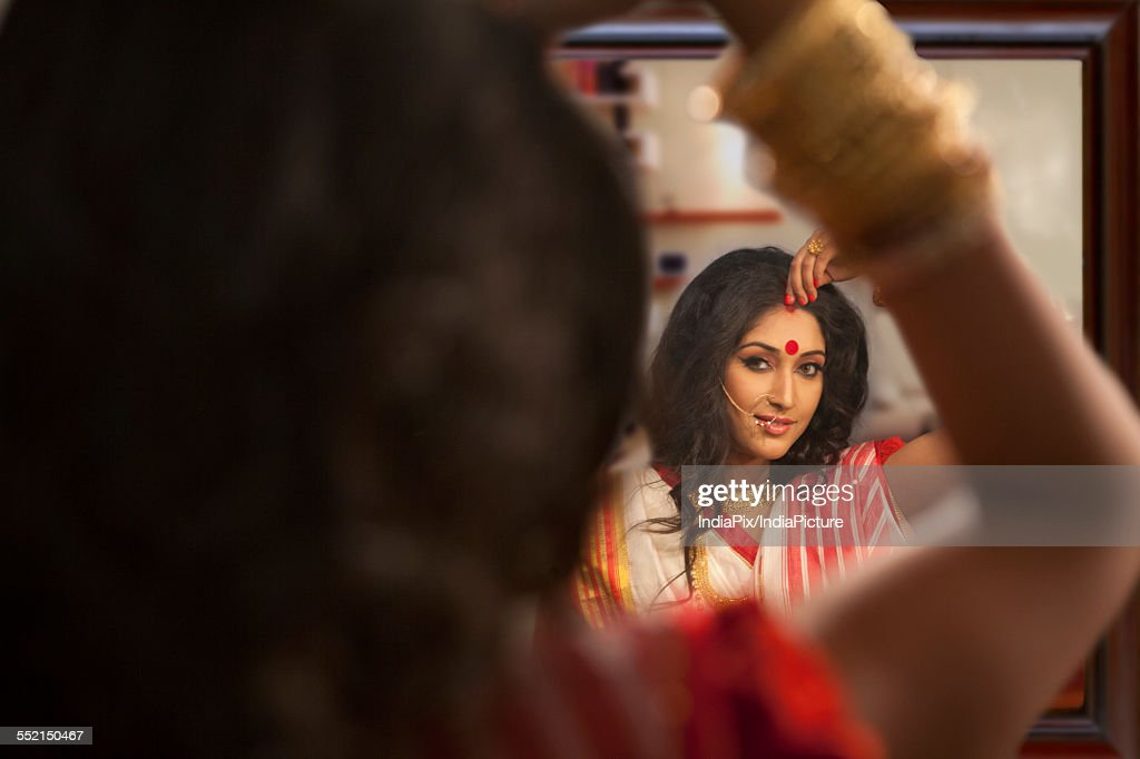 Bengali Woman Putting Sindoor On Her Forehead Stock Photo - Getty Images