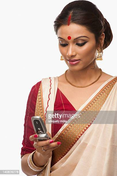 Bengali woman text messaging on a mobile phone